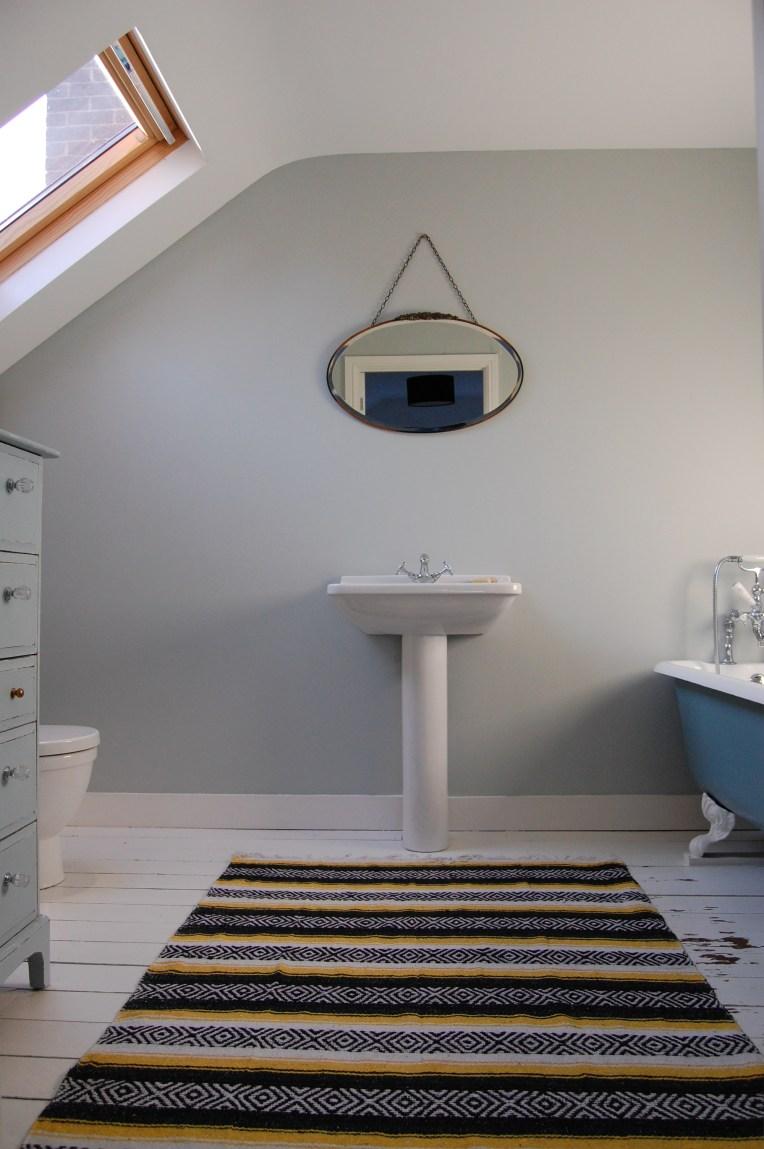 bathroom painted floor vintage mirror roll top bath Mexican rug