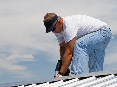 Construction worker uses a power drill to attach a cap the the top of a sheet metal roofing job with screws.