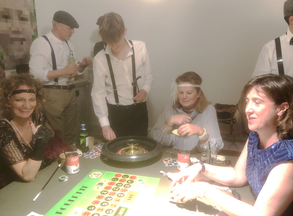 People in 1920s clothes playing roulette in a casino at speakeasy party