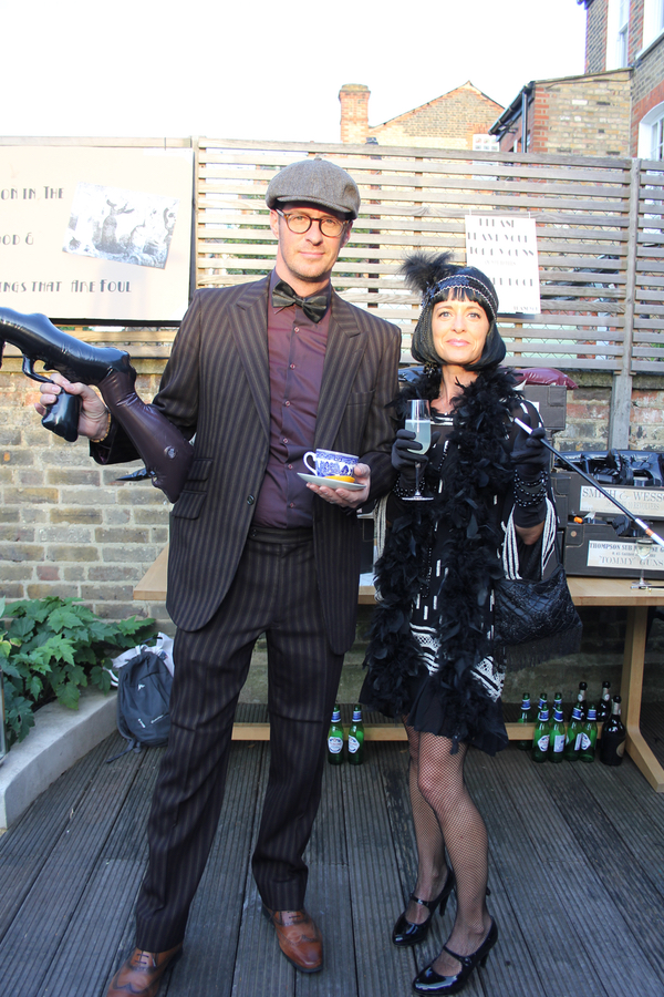 Gangster and gansters moll drinking gin from tea cups at speakeasy party