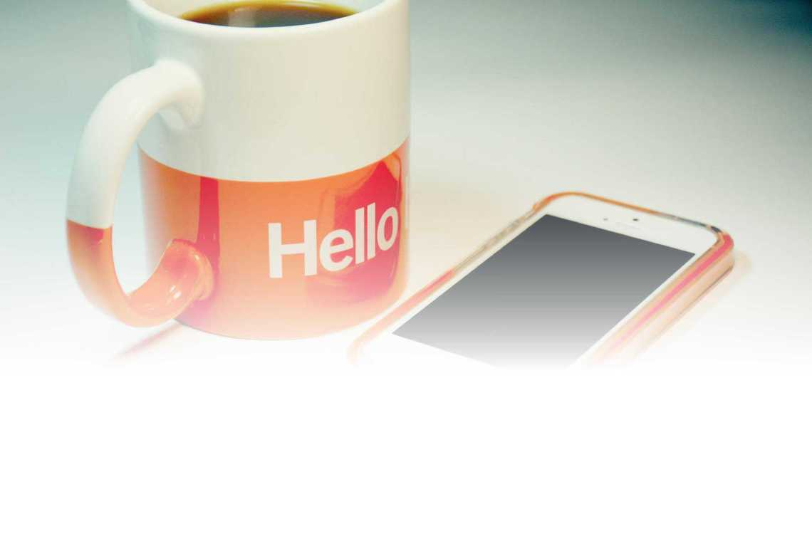 Cup of coffee and cellphone for the best free apps for moms.