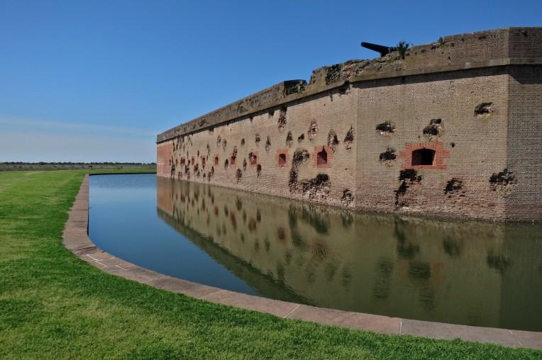 Scarred wall silently speaks of battle