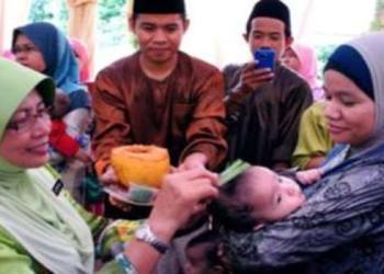 Seorang bayi sedang ditepung tawar dan dicukur jambulnya semasa adat naik buai.
