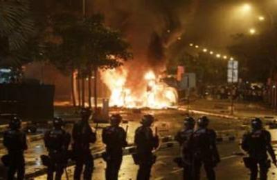 Polis sedang mengawal keadaan sambil memerhati sebuah kereta yang terbakar selepas satu rusuhan berlaku di Little India, Singapura, malam Ahad. Rusuhan tersebut berlaku selepas seorang pekerja warga India maut dilanggar sebuah bas, lapor agensi berita negara itu.