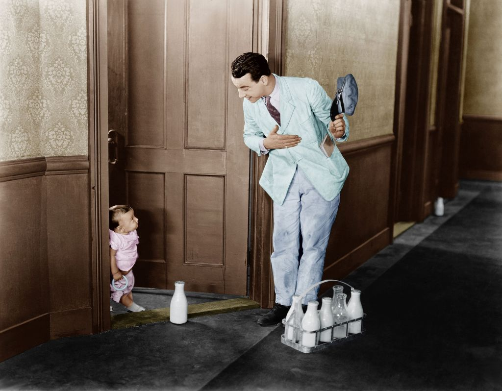 A milk delivery man on his daily delivery run. He places the milk bottle down with gratitude as a young child looks at him.