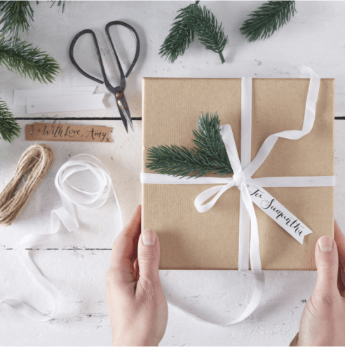 A custom sustainable gift package with a tree sprig decoration placed on top.