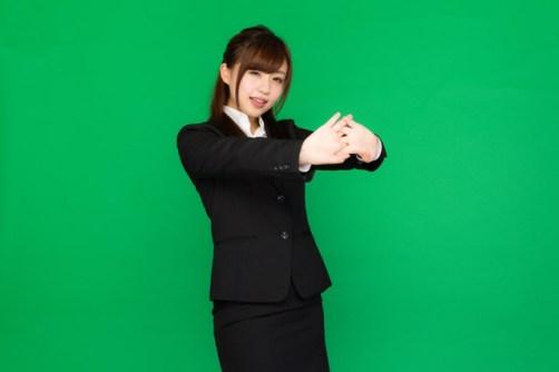 肩こりが酷くて両手を前に出して伸びをする事務の女性(グリーンバック)