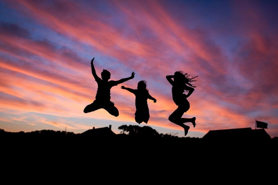 trz osoby skaczące na tle wieczornego nieba