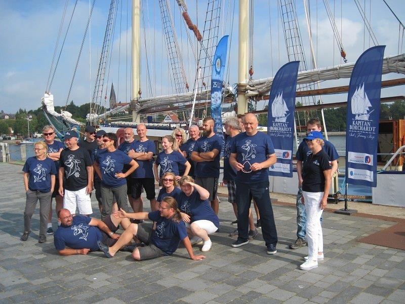 Wspólne zdjęcie kadry nauczycieli SKEM wraz zzałogą wgranatowych koszulkach rejsowych nakei przedżaglowcem