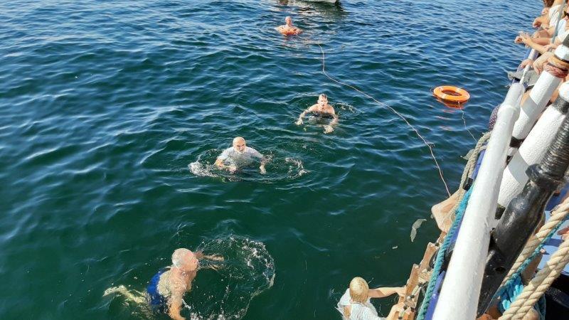 Zdjęcie zburty statku, wmorzu kąpie się pięć osób, dwa koła ratunkowe pływają wpobliżu