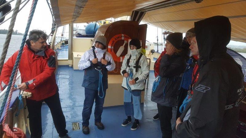 Oficer Marcin przeprowadza szkolenie naśródokręciu dla Iwachty zprawidłowego wpinania się pasami doelementów stałych