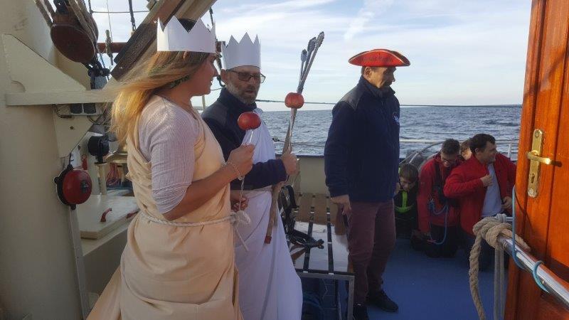 Na śródokręciu napierwszym planie jest Neptun wraz zProzerpiną orazkapitan żaglowca. Obok nich widać klęczących uczniów uczestników Chrztu Morskiego .W tle widać morze aż pohoryzont.