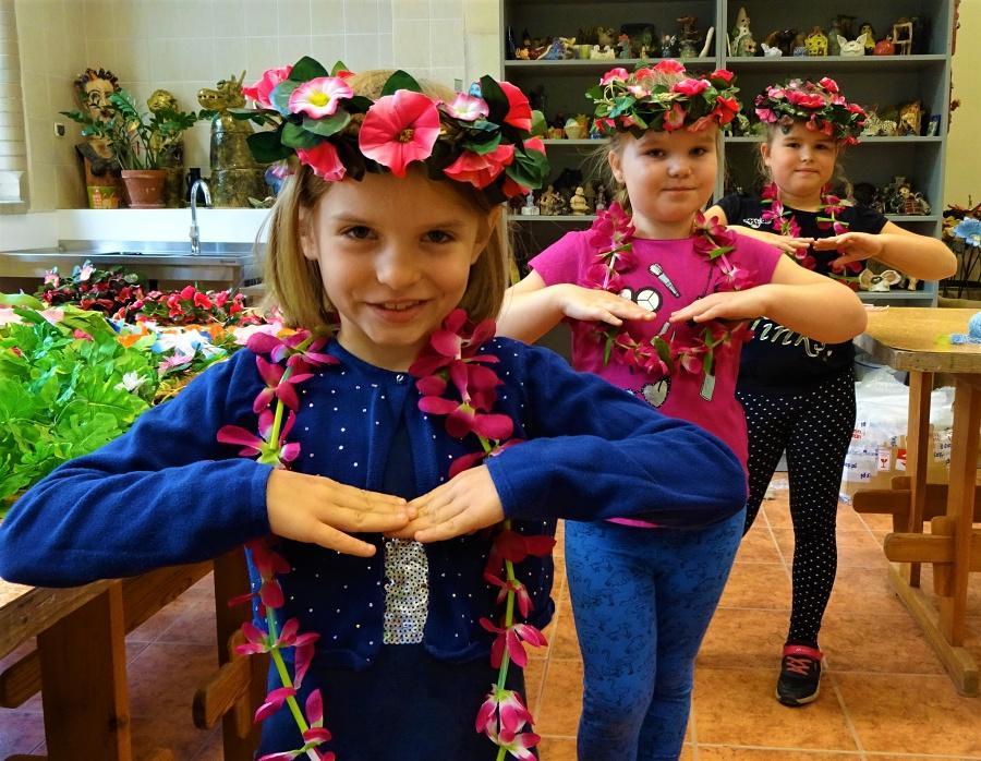 trzy dziewczynki stojące jedna zadrugą wpozycji tanecznej. Nagłowach mają wianki zróżowymi kwiatkami, anaszyi zawieszone girlandy zróżowych płatków.