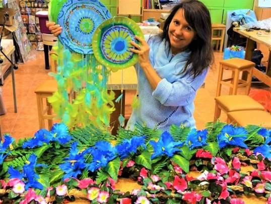 kobieta siedząca przy stole układająca kompozycje zniebiesko-turkusowych kwiatów nazielonych liściach. Nastole leżą bukiety niebieskich kwiatów iliści.