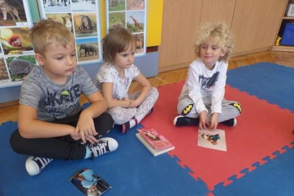 trójka dzieci siedzi namacie, przeddwójką znich leżą fotografie ich zwierząt, dziewczynka ma przedsobą książkę ozwierzętach