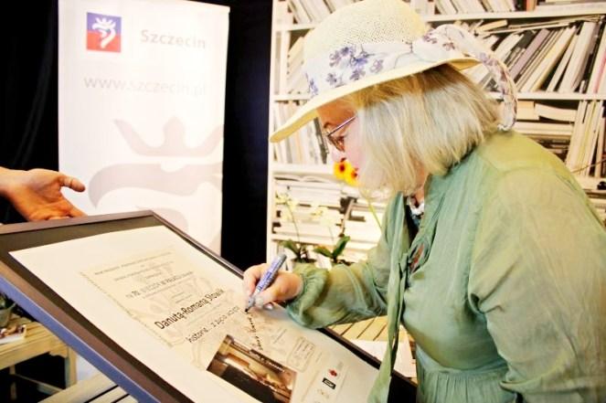 Autorka podpisuje plakat promujący spotkanie literackie