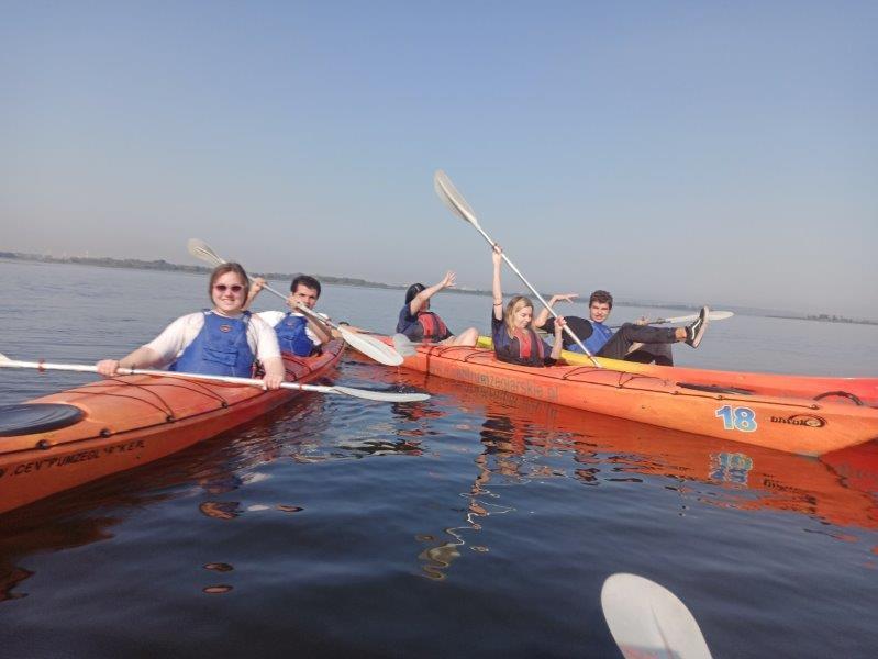 Na jeziorze trzy pomarańczowe kajaki z uśmiechniętymi uczniami Szkolnego Koła Edukacji Morskiej z Technikum Ekonomicznego na wodzie w kajaku