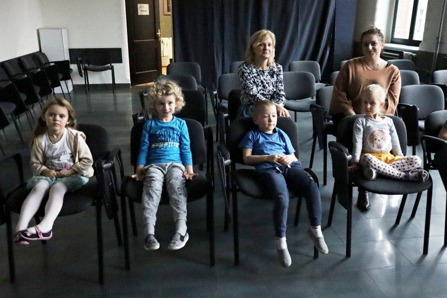 przedszkolaki siedzące nakrzesłach ztyłu nauczycielki