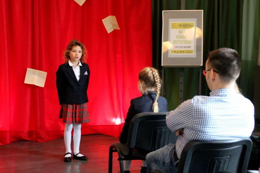 Dziewczynka na tle czerwonej zasłony na pierwszym planie dwie osby siedzące na krzesłach