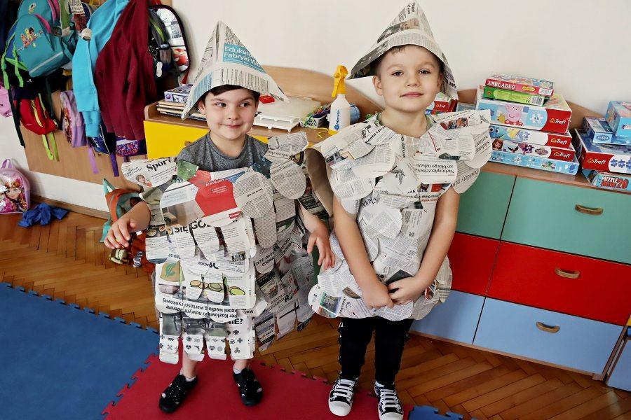 dwoje dzieci wstrojach zrobionych zgazety