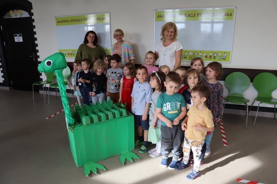 grupa przedszkolaków z nauczycielkami pozuje z kartonowym diznozaurem
