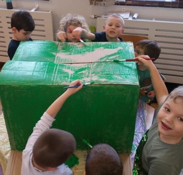 grupa przedszkolaków maluje nazieolono karton