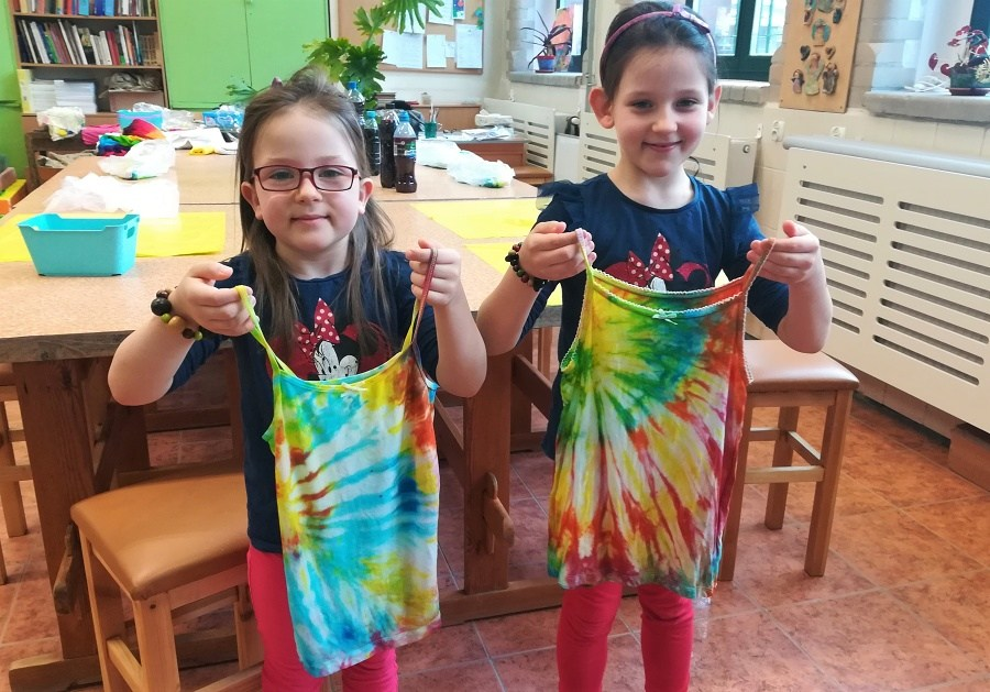 Trzy uśmiechnięte dziewczynki stoją w sali obok siebie trzymając kolorowe, farbowane bluzki