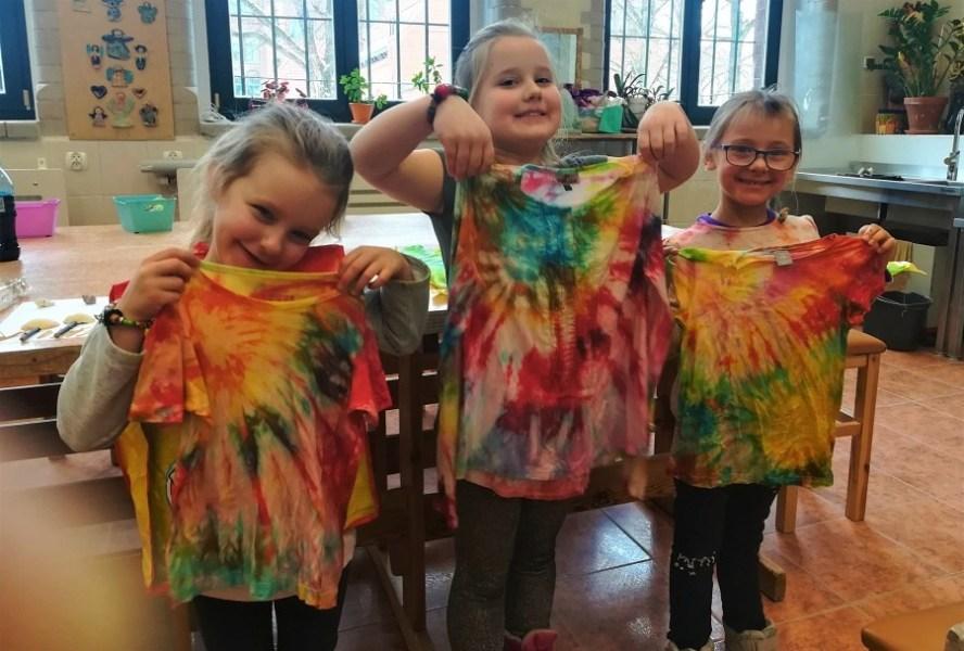 trzy dziewczynki stoją obok siebie trzymając zabarwione koszulki
