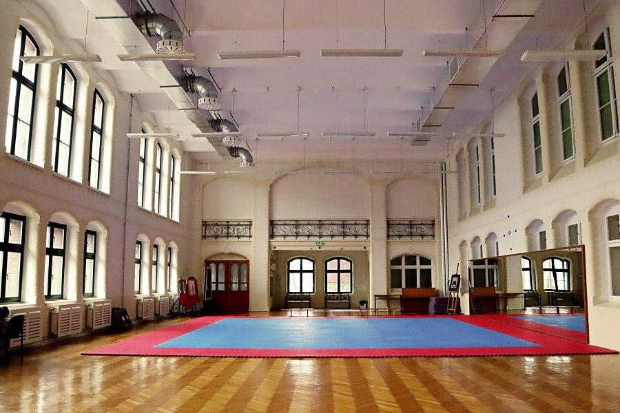 wnętrze salu gimnastycznej wPałacu Młodzieży, naśrodku duż mata niebiesko-czerwona