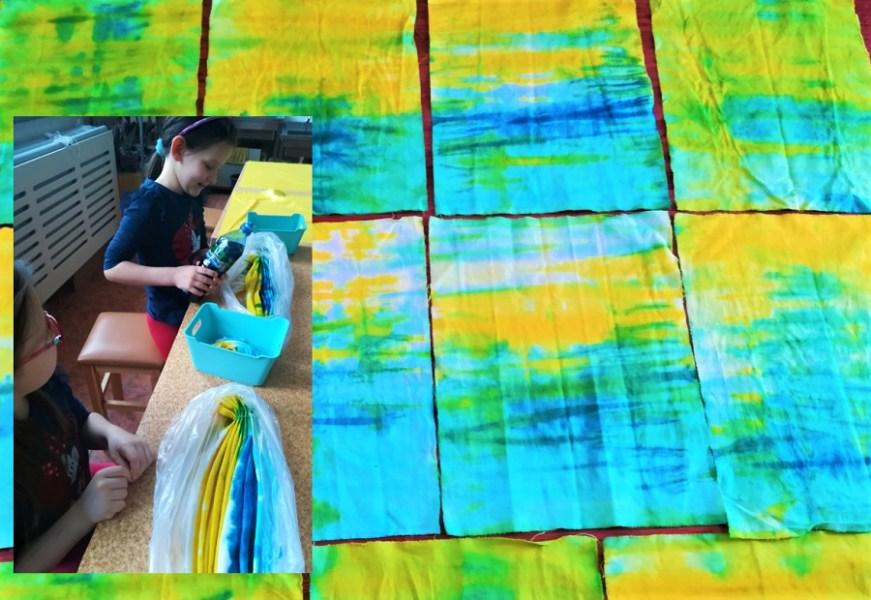 W lewym boku zdjęcia dwie dziewczynki. Jedna siedzi, adruga stoi trzymając butelkę zbarwnikiem. Przednimi wfoliowych woreczkach barwna tkanina. Tło stanowią tkaniny pofarbowane nakolor żółto-niebieski