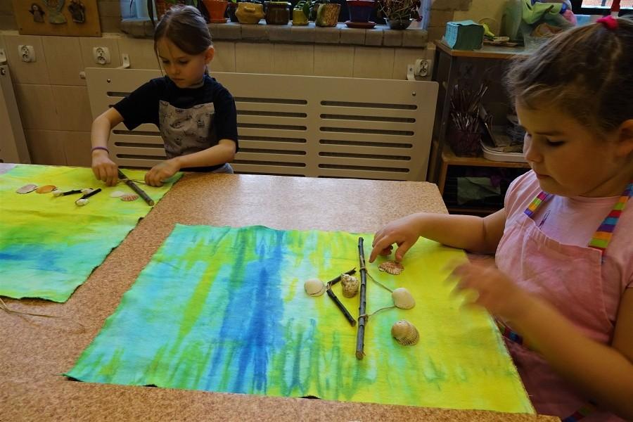 Dwie dziewczynki siedzące przy stole układające kompozycje z muszli, patyków i sznurków na żółto-niebieskich tkaninach.