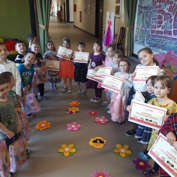 grupa przedszkolaków dziewczynki zdplomami wrękach