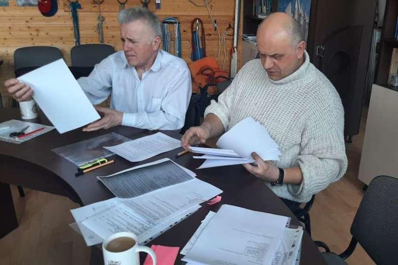 nauczyciele siedzący przy stole przeglądają dokumentację