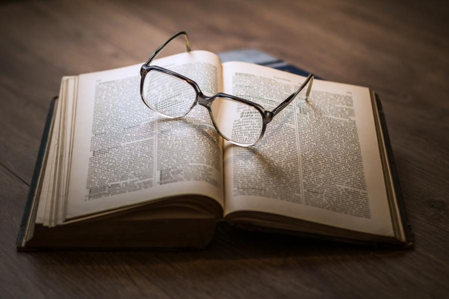 rozłożona książka a na niej okulary