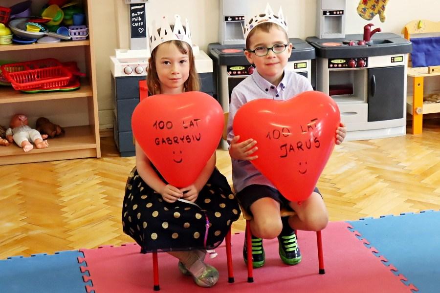 chłopiec i dziewczynka w koroanach na głowei, trzymają balony w kształcie serca