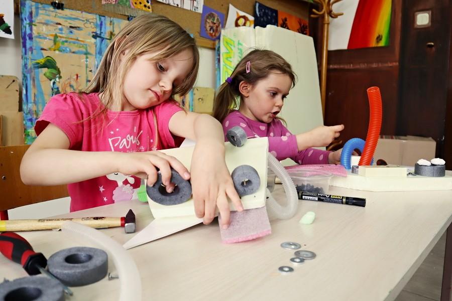 dwie dziewczynki siedzące przy stole podczas konstruouwania