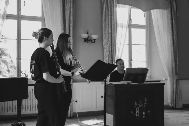 dwie dziewczyny grające naflecie wtle mężczyzna przedinstrumentem