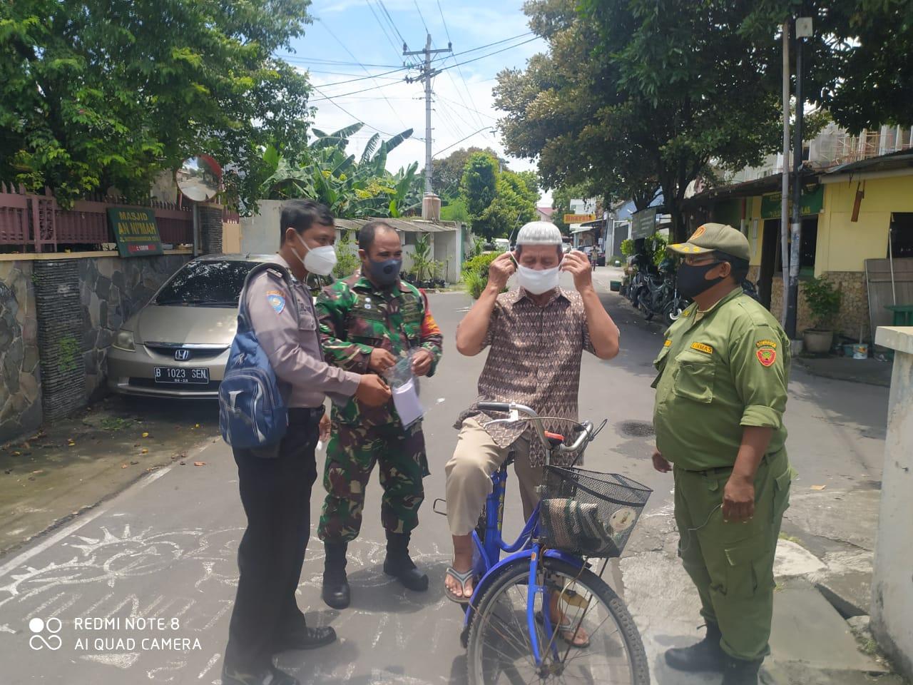 Babinsa dan Bhabinkamtibmas Kemlayan Susuri Jalan Kampung Sambil Sosialisasikan PPKM dan Bagikan Masker
