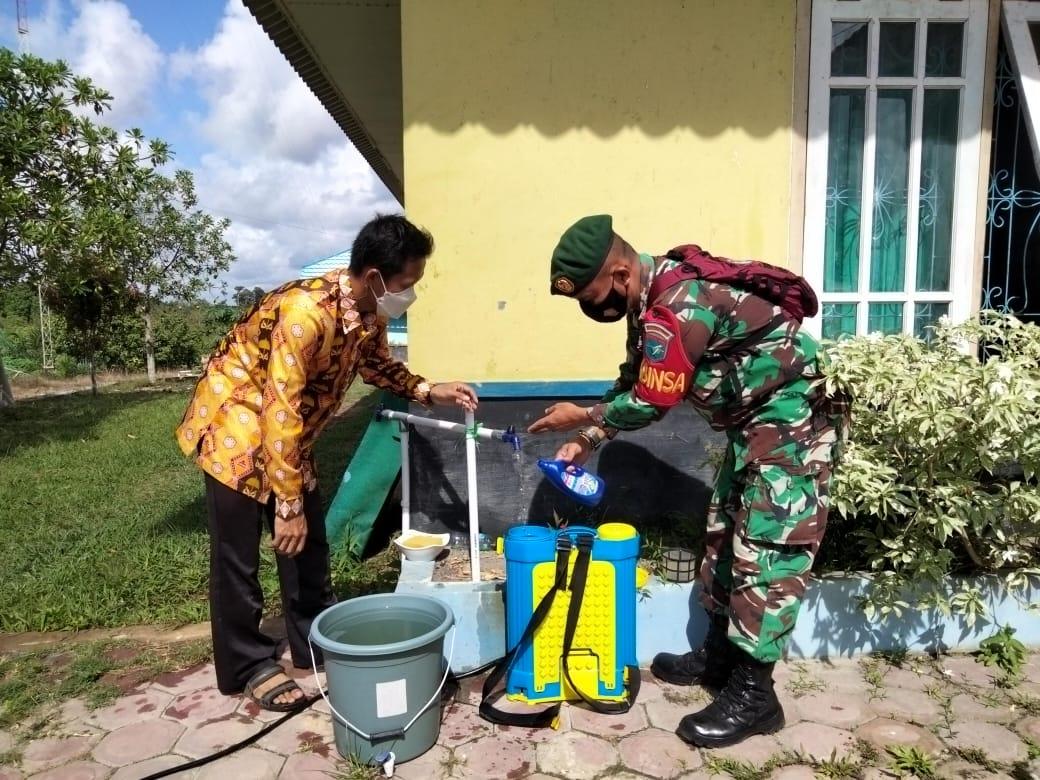 Babinsa Lakukan Penyemprotan Disinfektan Kerumah Warga  Desa Runtu