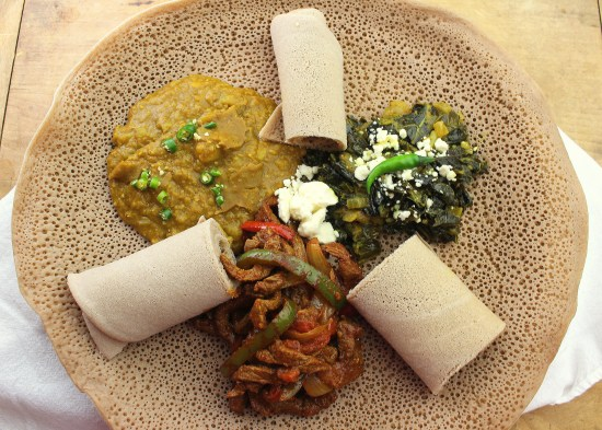 Ethiopian Meal of Misir Wot, Rolls of Injera bread, Gomen, Beef Tibs, all on a larger round of Injera Bread