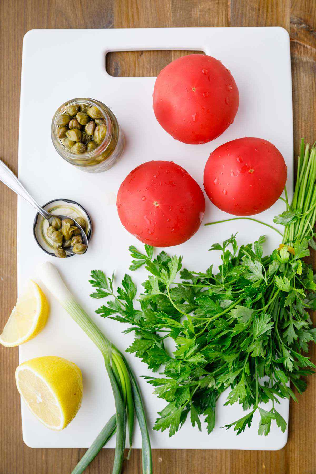 prepping tomato and caper salsa ingredients