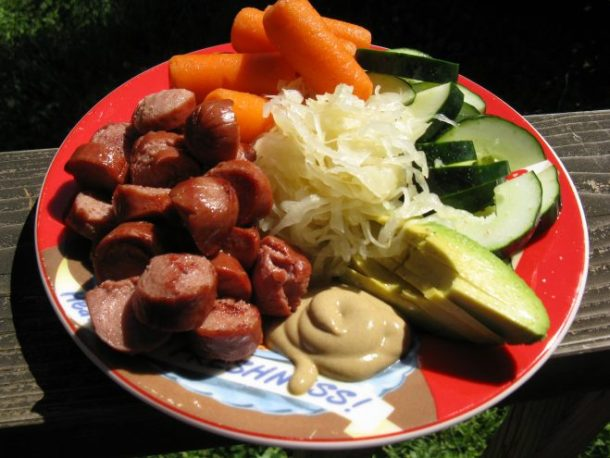 Two grass-fed beef hot dogs, sauerkraut, avocado, cucumber slices, carrots and Dijon mustard.
