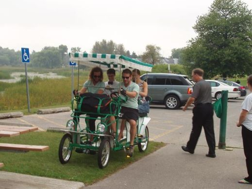 "Our surprise bike chariot that took us to the reception. My brother in-law and friend wore matching outfits and rode us all the way there. There was a ""newly married"" sign and cans hanging off the back."