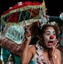 """Alessandra Nogueira (Neguinha): Entrou para o Grupo Palhaços Trovadores em 2001, mas antes disso já havia feito diversos trabalhos em teatro. Foi convidada também para participar de espetáculos de outros grupos. Nos últimos dois anos, participou dos seguintes trabalhos: – Cidade das Mulheres, Chico das Mangueiras (2002). Direção: Miguel Santa Brígida – Grupo E.L.A. e a Poesia (2001-2003). Direção: Grupo E.L.A. (Alessandra Nogueira, Landa de Mendonça e Érica Oliveira) – Olho de Peixe Boto (2002). Direção: Paulo Ricardo e Adriana Cruz. – Ele não Sabe que seu Dia é Hoje (2005). Direção: Adriano Barroso. Trabalhou como professora substituta na Escola de Teatro e Dança da UFPA nos anos de 2005 e 2006. Também vem participando de encontros com atores e pesquisadores do grupo Lume, de Campinas/SP, fazendo os treinamentos sobre metodologia para ator, treinamento técnico e    energético do ator. Em março de 2012, participou do """"Esse monte de mulher palhaça"""" – Festival Internacional de Comicidade Feminina, organizado pelo grupo do Rio de Janeiro As Marias da Graça. Apresentou, junto com três trovadoras, a número tradicional de circo """"Morrer para ganhar dinheiro"""" e participou da oficina The Dance and The Clown, ministrada pela canadense Grindl Kuchirka. Além de atriz-palhaça, exerce a função de Diretora Executiva do grupo e a de coordenadora do projeto """"Palhaçadas de Quinta"""". Tem formação Acadêmica em: Especialização em Estudos Contemporâneos do Corpo. Instituto de Ciências das Artes-ICA/UFPA; Especialização em Psicomotricidade. Universidade Estadual do Pará – UEPA; Terapia Ocupacional – Instituição de ensino: Universidade Estadual do Pará-UEPA; Curso Complementar: Curso Técnico de Formação de Ator da Escola de Teatro da Universidade Federal do Pará – ETDUFPA."""