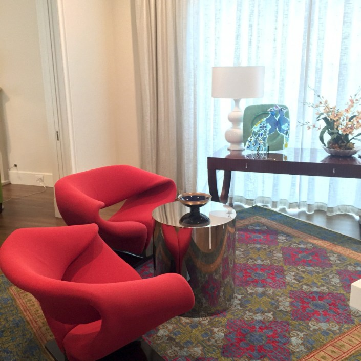 Contemporary red chairs and chrome end table