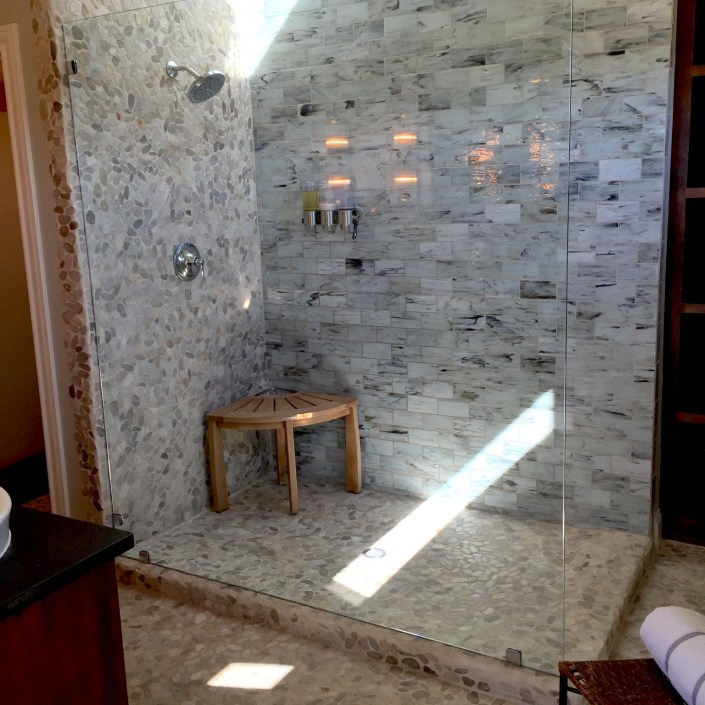 Modern shower design with stone mosaic backsplash