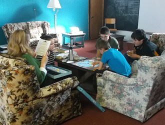 Four grade 7 & 8 students - 3 boys and a girl - along with their Sunday School teacher, gathered around a board game