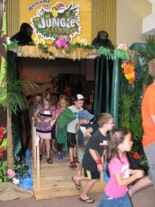 Several children exiting a doorway that has been decorated with a jungle theme for their Vacation Bible School program