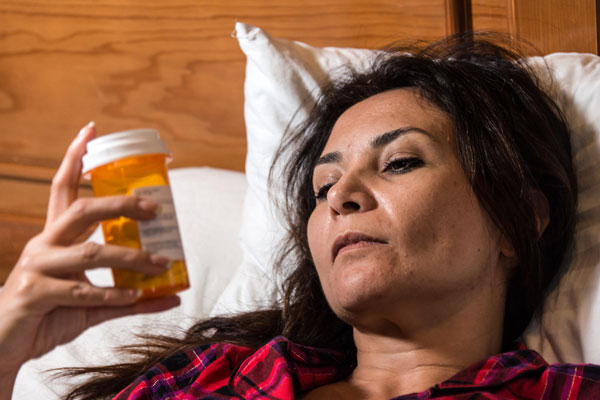 woman looking at prescription of sleeping pills