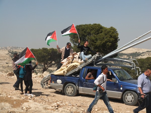 Demonstrators arrive with materials to build new village